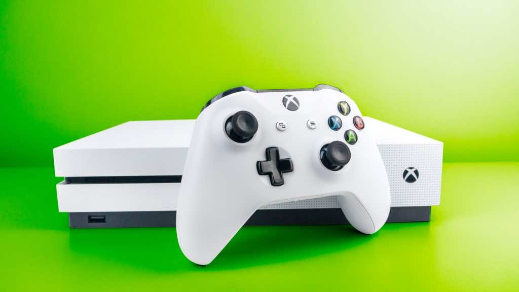 White xbox controller in front of xbox one console