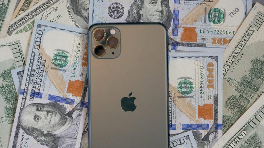 iPhone 12 with dollar bills